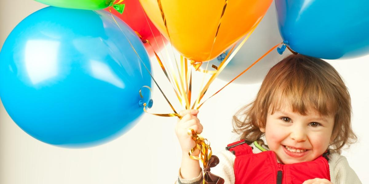 small girl with party balloons